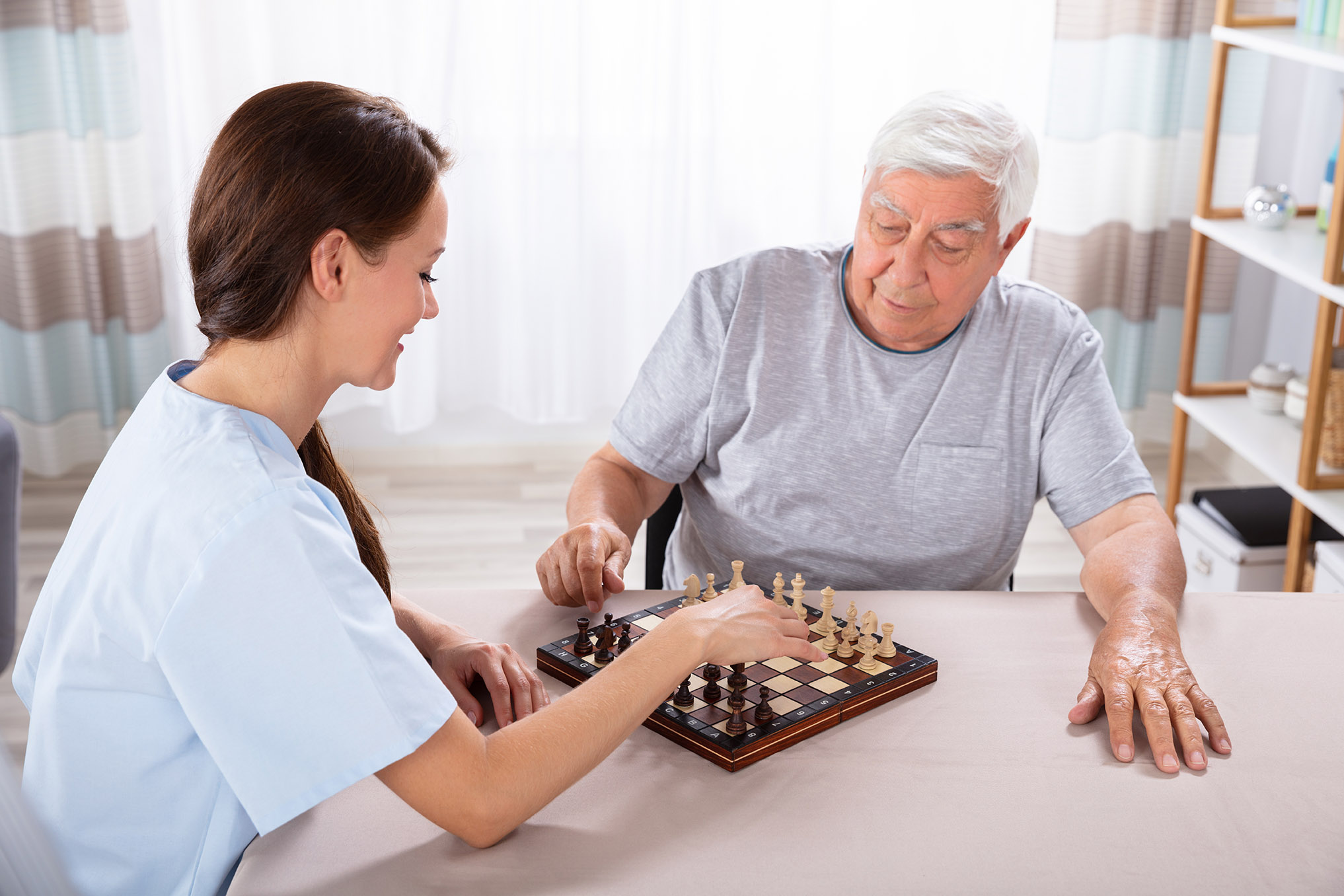 Female Caretaker Playing Chess With Senior Man