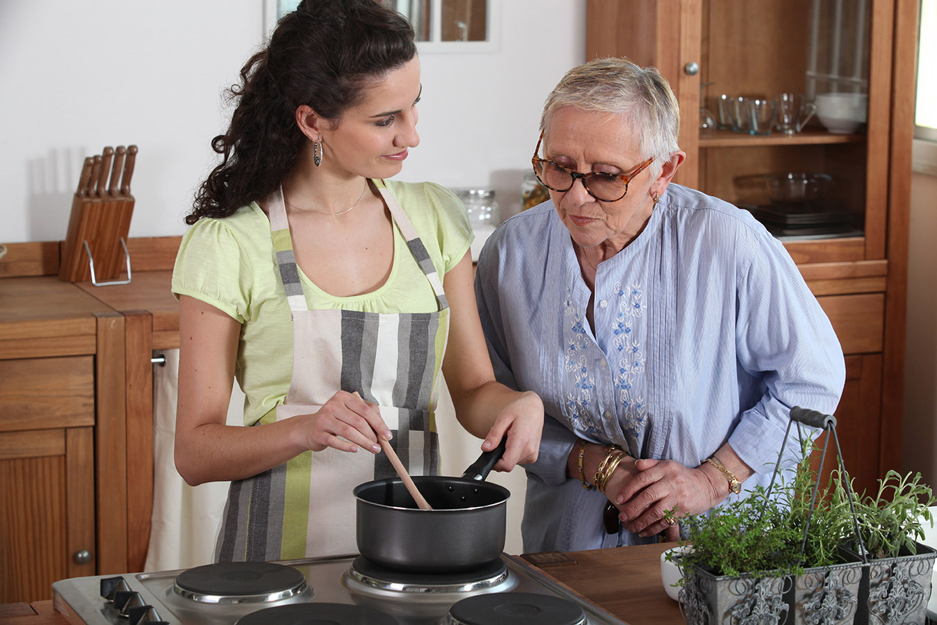 Young woman cooking for an elderly lady